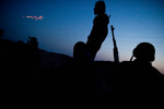 Libyan rebels watch tracers and anti-aircraft rounds fly across the evening sky at pro-Gaddafi forces.
