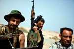 Libyan rebel soldiers stands along a barren strech of seacoast road following a rebel retreat from Bin Jawad.