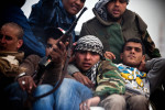 Packed into the back of a rebel truck, soldiers flee a Gaddafi loyalist ambush.