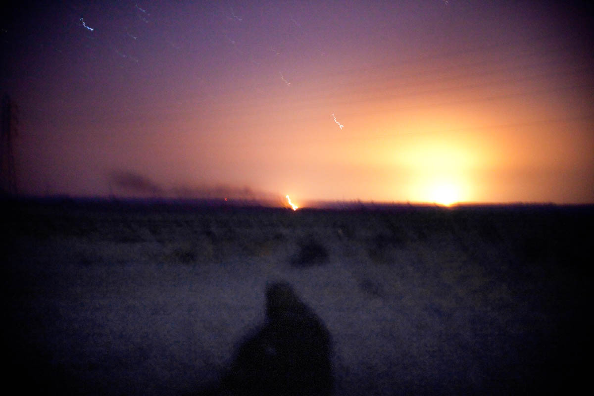 A Libyan rebel watches the impact and explosion from both NATO ordinance and rebel anti-aircraft rounds.