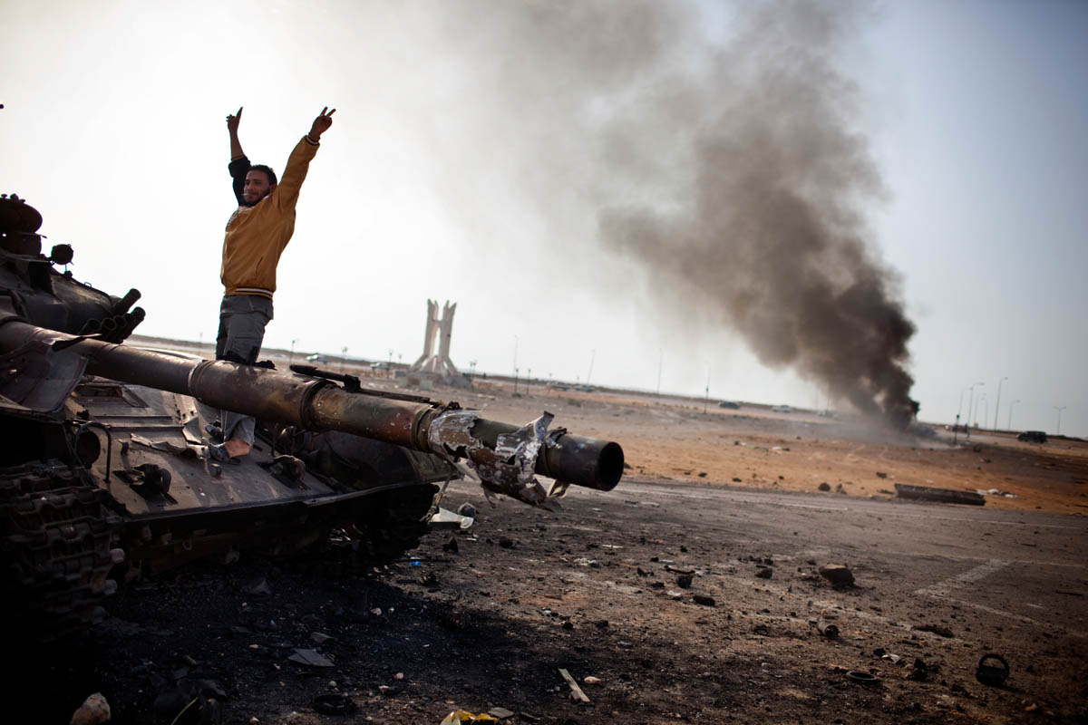 While standing on a burned out loyalist tank, a Libyan celebrates the fall of Ajdabiya to rebel forces.