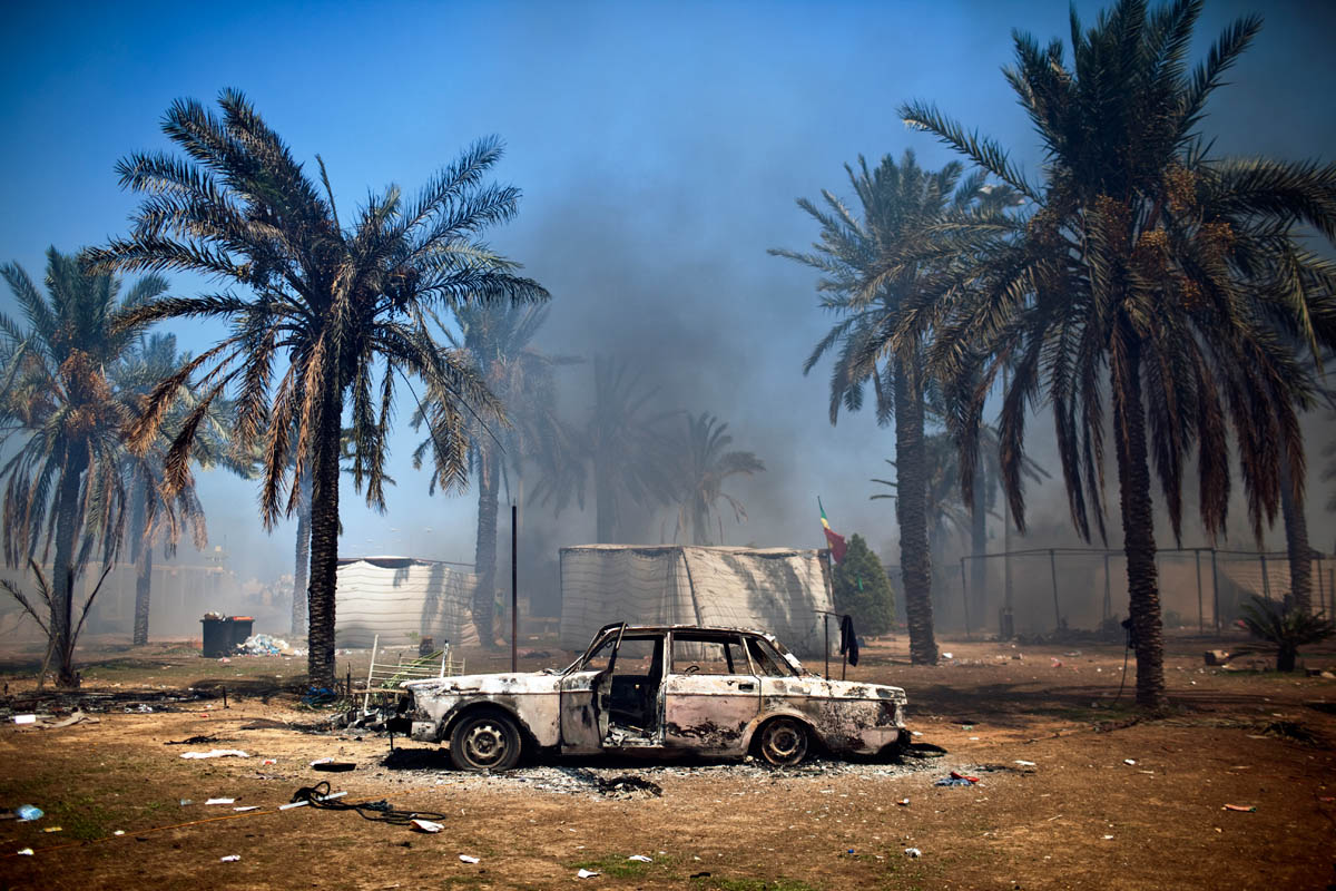 A car lies tourched along with a Gaddafi loyalist encampment in the roundabout outside the Bab al-Aziziya compound.