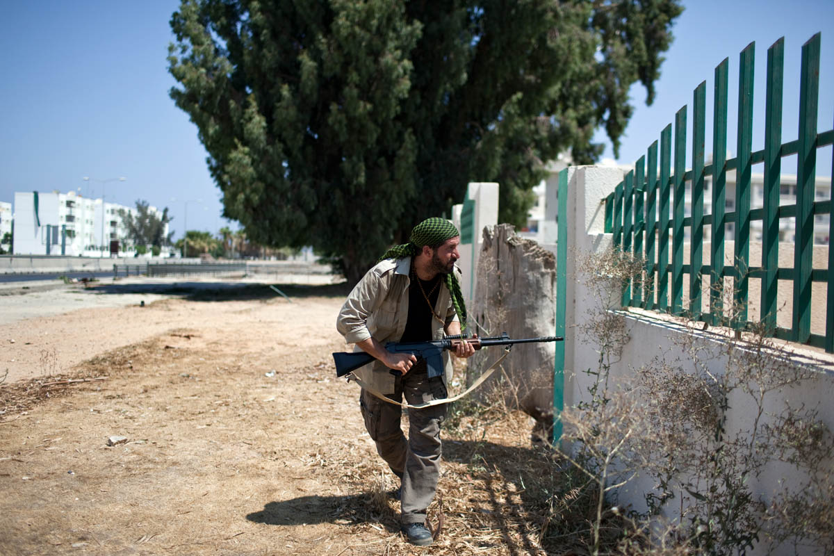 A rebel sniper watches for a suspected pro-Gaddafi loyalist position during a gun battle in Tripoli's Abu Salim neighborhood.