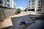 The body of a recently killed pro-Gaddafi sniper lies outside an apartment complex near the south entrance of the Bab al-Aziziya compound.