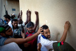 uspected Gaddafi loyalist soldiers are pulled from apartments and lined up against a wall in the Abu Salim neighborhood by rebel forces on August 25 2011 in Tripoli, Libya. The suspected loyalist soldiers were made to chant {quote}Allah-O-Akbar{quote} and were repeatidly pushed, punched and shoved by the rebels, before they were driven away in a pickup truck.