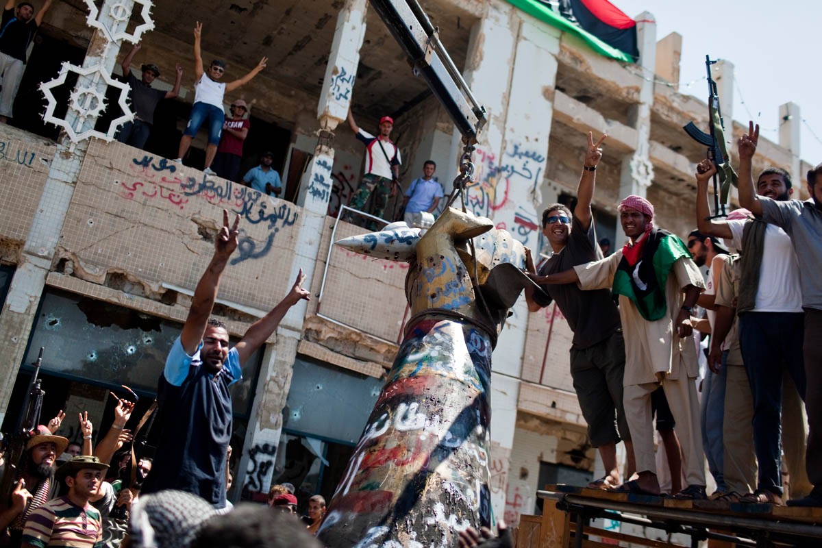 Libyans raise their arms in celebration as they tear down Gaddafi's infamous {quote}hand crushing a plane{quote} statue.