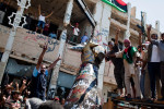 Libyans raise their arms in celebration as they tear down Gaddafi's infamous
