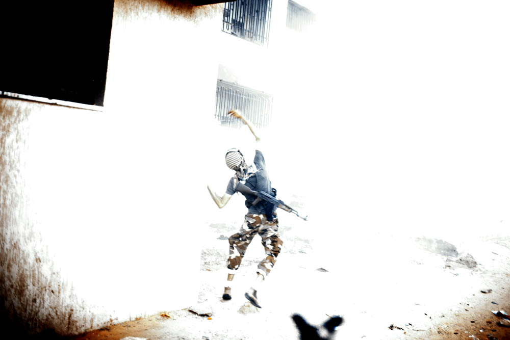 A Libyan rebel throws a grenade toward an apartment building housing Gaddafi loyalist soldiers.