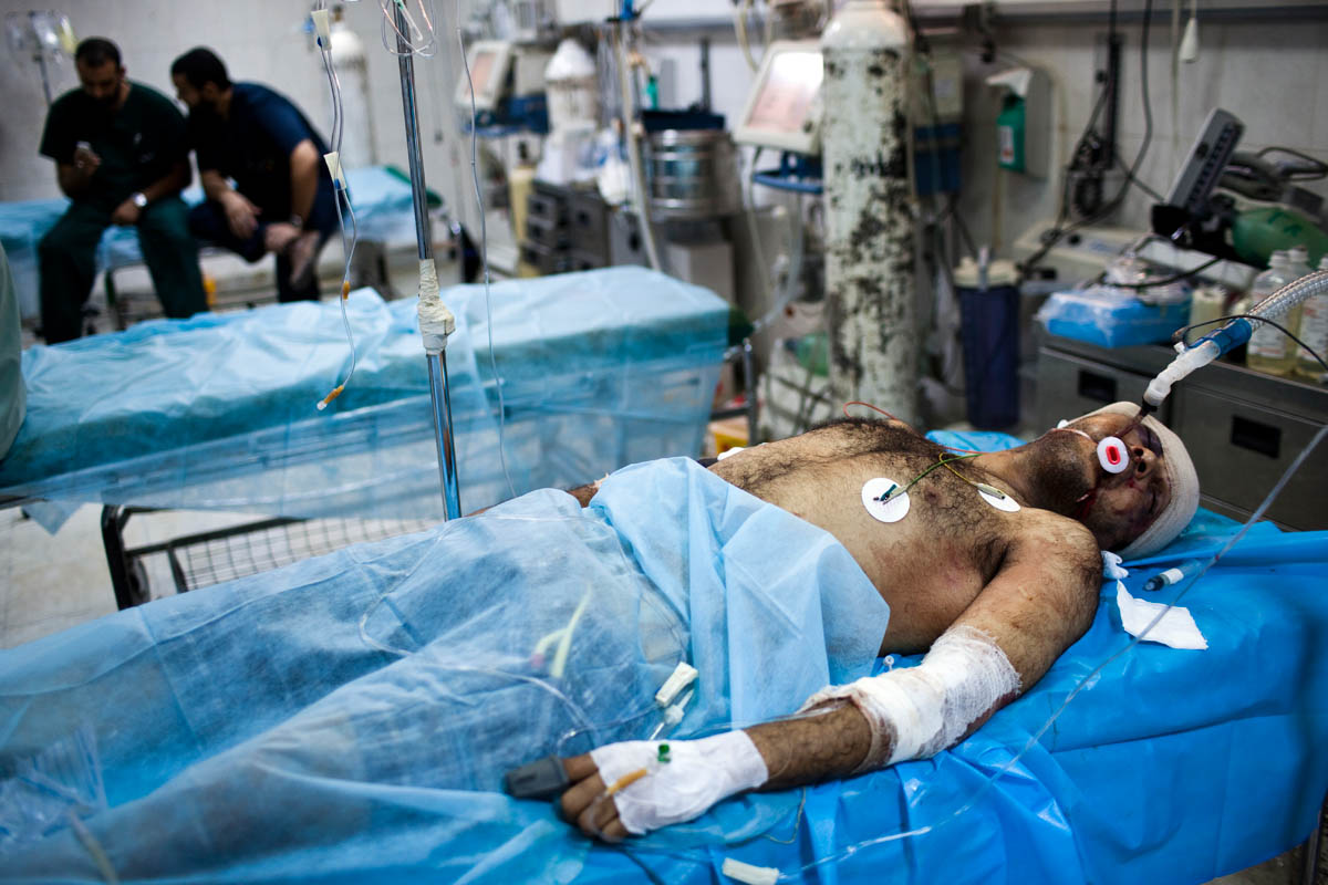 A Libyan man, shot in the head, is treated at a hospital ICU ward.
