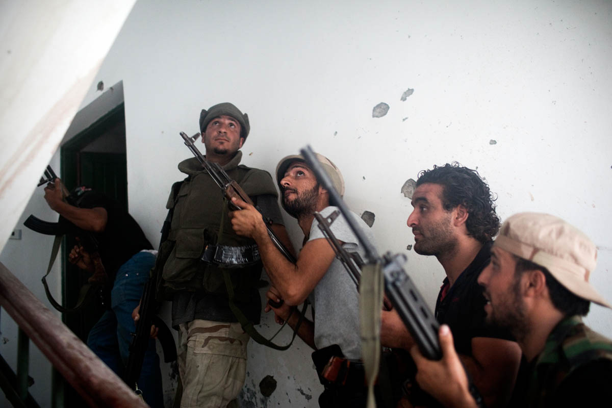 A group of Libyan rebels line up in a cramped stairway during an apartment clearing operation to kill a Gaddafi loyalist sniper hiding out on the floor above.