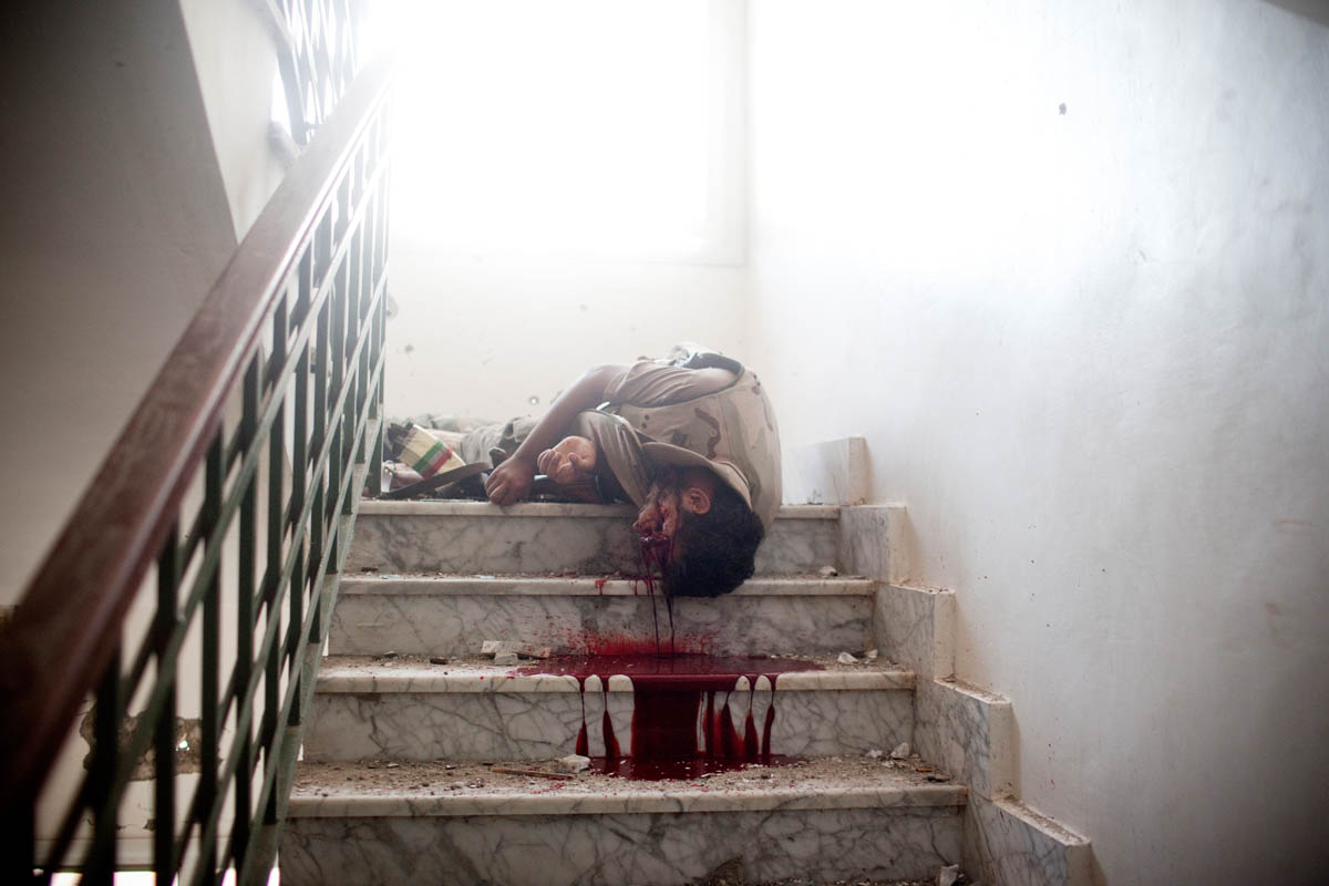 The body of a Libyan rebel lies on the floor of a cramped stairwell after being shot by a Gaddafi loyalist sniper.