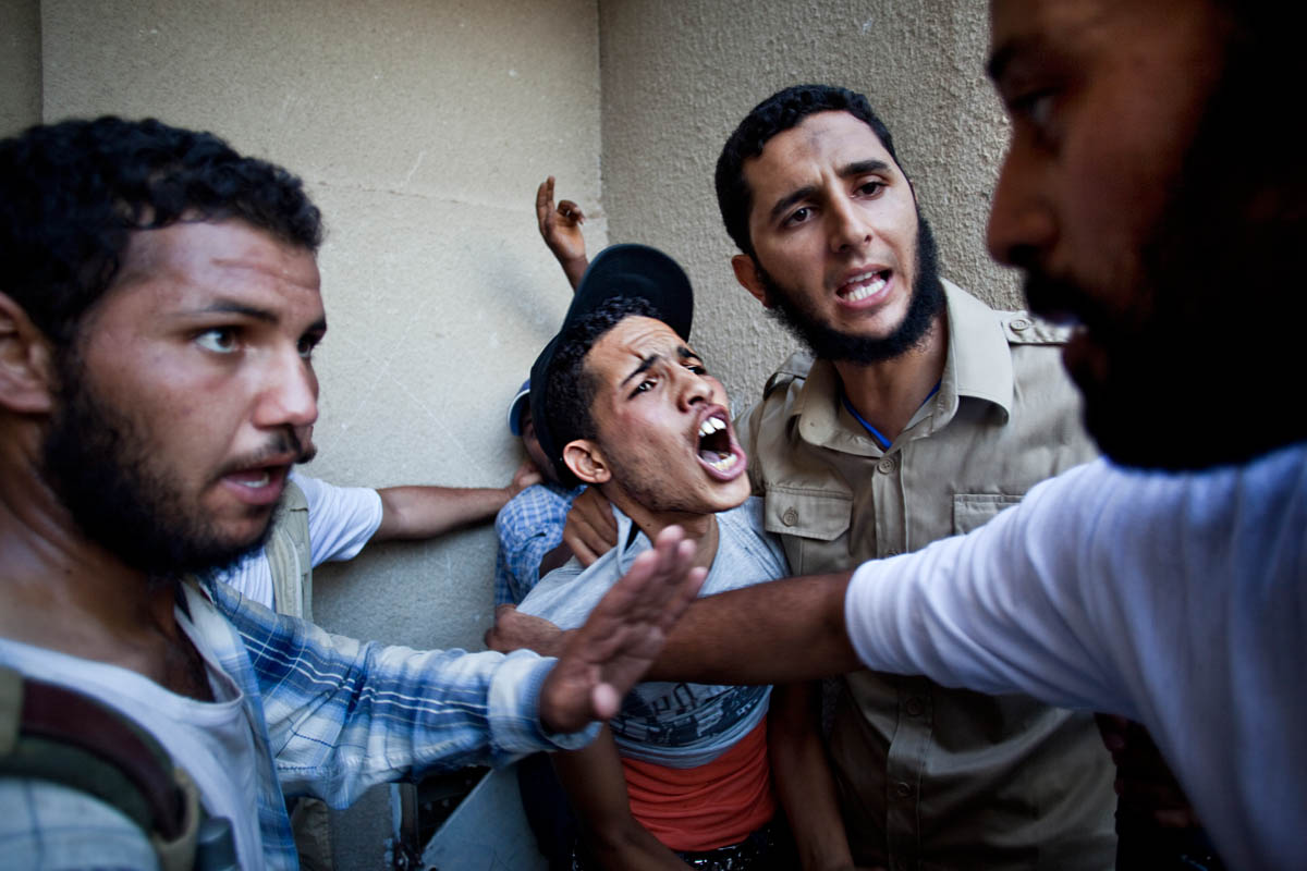 A young Libyan, suspected of being a Gaddafi loyalist, is arrested by rebel forces.