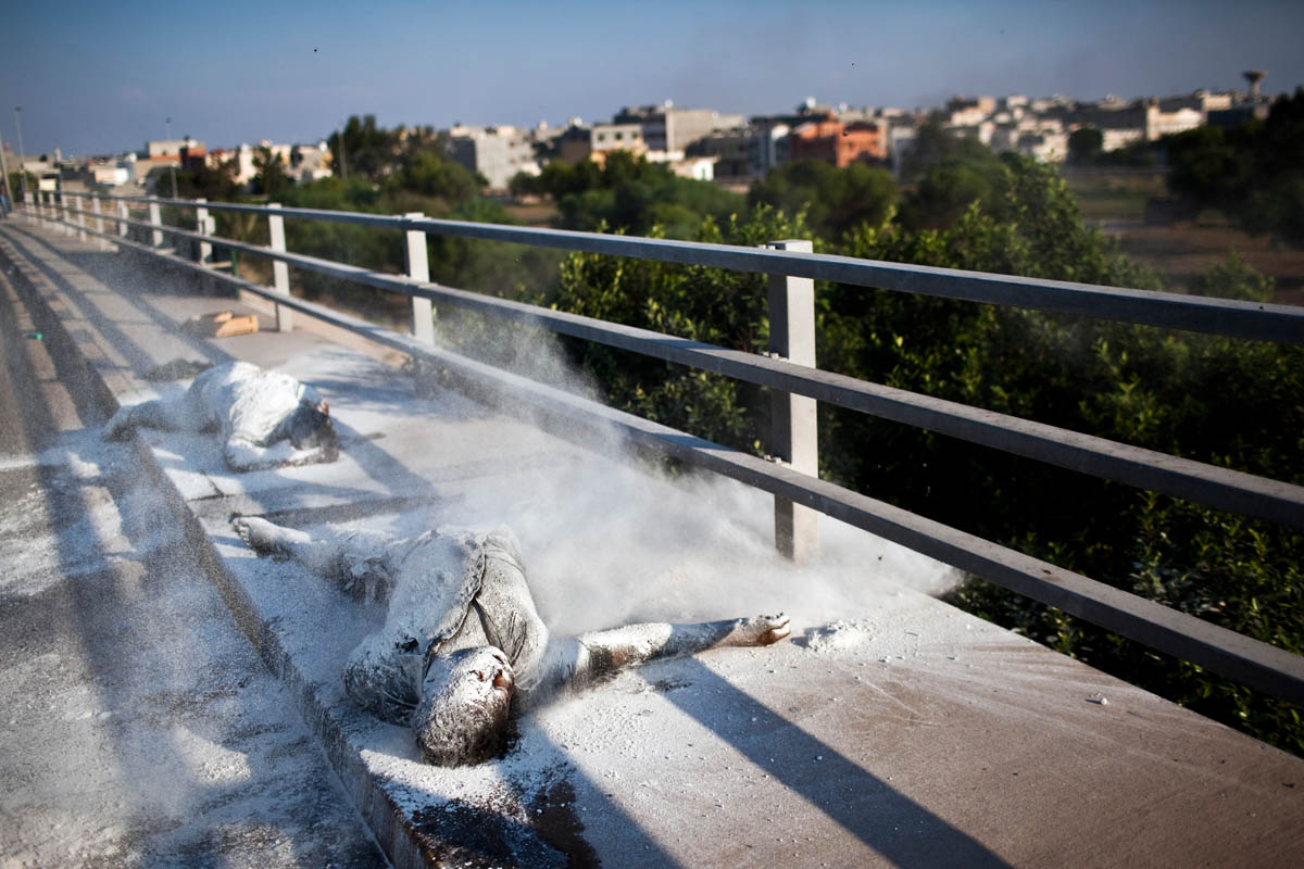 The body of a dead Libyan, the victim of a sniper, lies covered in lime on a traffic overpass in Tripoli.