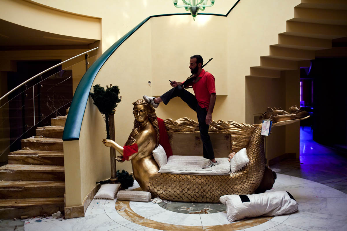 A Libyan rebel stands and poses on an ornate mermaid loveseat, a wedding gift made to resemble Aisha Gaddafi, daughter of former Libyan dictator Moammar Gaddafi.