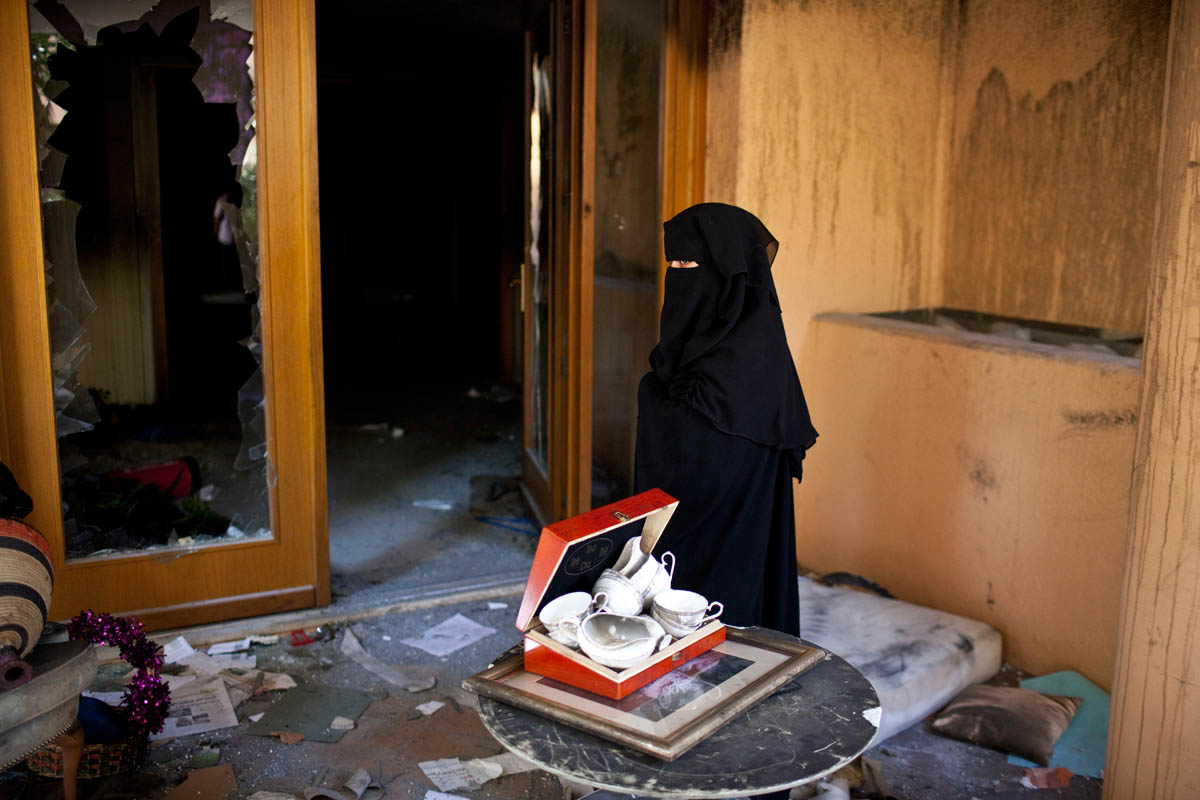 A veiled Libyan woman stands next to several looted serving bowls in the main doorway of former Libyan dictator Moammar Gaddafi's home.