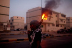 A Libyan rebel stands in front of a burning building following the rebel victory in Tripoli.