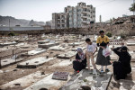 A family prays at a grave neighboring the final resting place of former Guantanamo inmate Adnan Latif in Taiz.