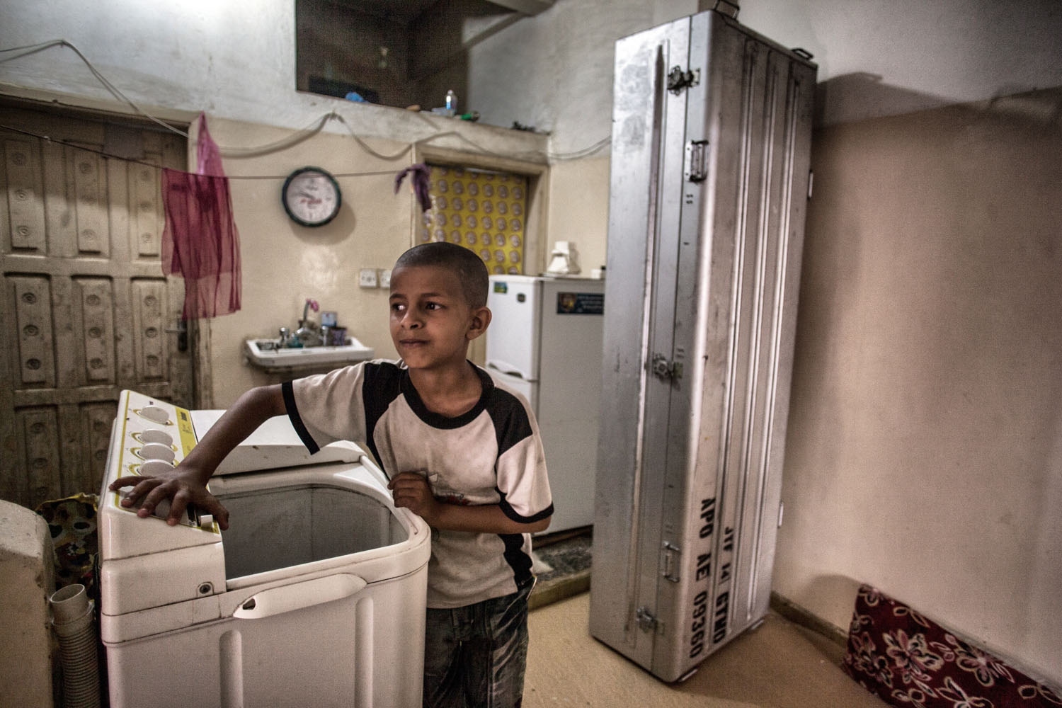 A young Latif family member stands next to the steel coffin that Adnan Latif's body was transported in, from Guantanamo back to Yemen in Taiz. The family has decided to keep the coffin in their laundry room and will not dispose of it until the truth of Adnan's death is made public.