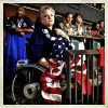 A disabled democrat hugs an American flag during the keynote address on the first night session of the Democratic National Convention.
