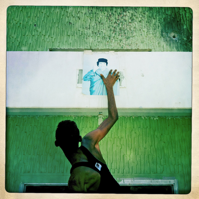 A Libyan rebel rips a poster of former dictator Moummar Gaddafi from the lobby of an apartment complex.