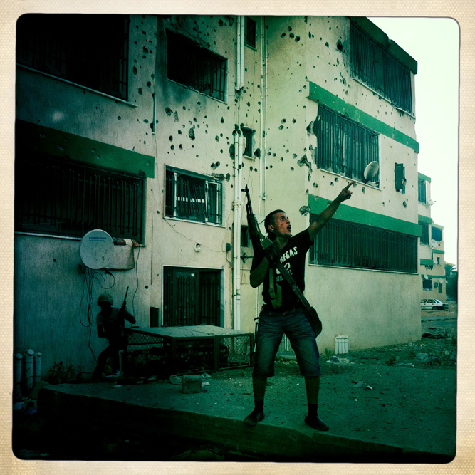 A Libyan rebel screams for rooftop fighters to fire on a building housing a Gaddafi loyalist sniper.
