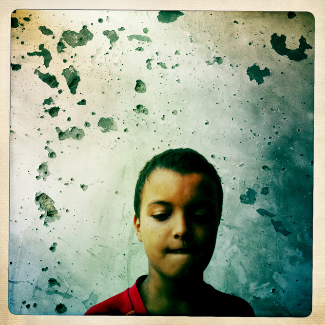 A Libyan boy stands infront of a bullet scarred wall in an apartment building targeted by Rebel forces during a violent confrontation with Gaddafi loyalists.