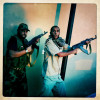 Libyan Rebels aim their weapons at a suspected Gaddafi loyalist sniper who targeted the Corninthian hotel.