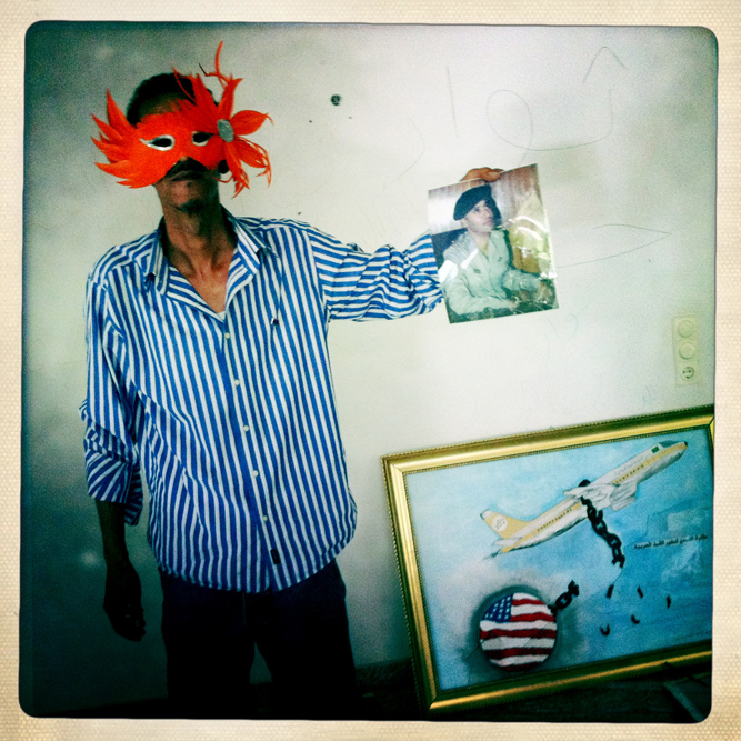 A masked Libyan holds up a picture of one of Moammar Gaddfi's sons in the bombed and looted home of Motasem Gaddafi.