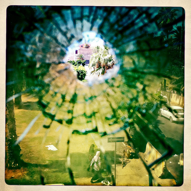 Two Libyan women walk through a park on the outskirts of Martyr's Square as seen through a bullet riddled window belonging to a Gaddafi government domestic spy office.