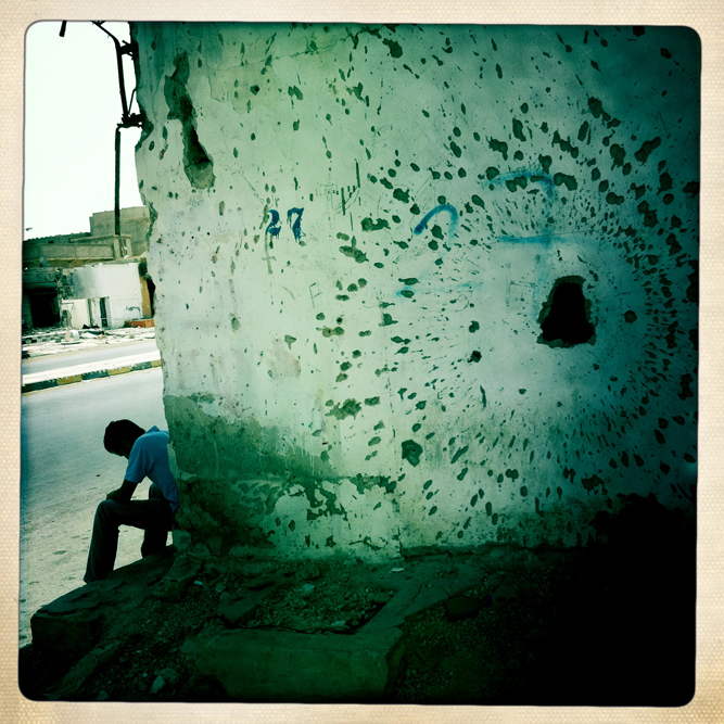 A Libyan man sits along a war ravaged Tripoli Street, surrounded by buildings pockmarked with mortar and bullet holes in Misrata, Libya.
