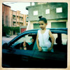 A young Libyan girls climbs outside a car window as a woman flashes a peace sign and honks her horn in celebration of the fall of Libyan Dicator Muammar Gaddafi.