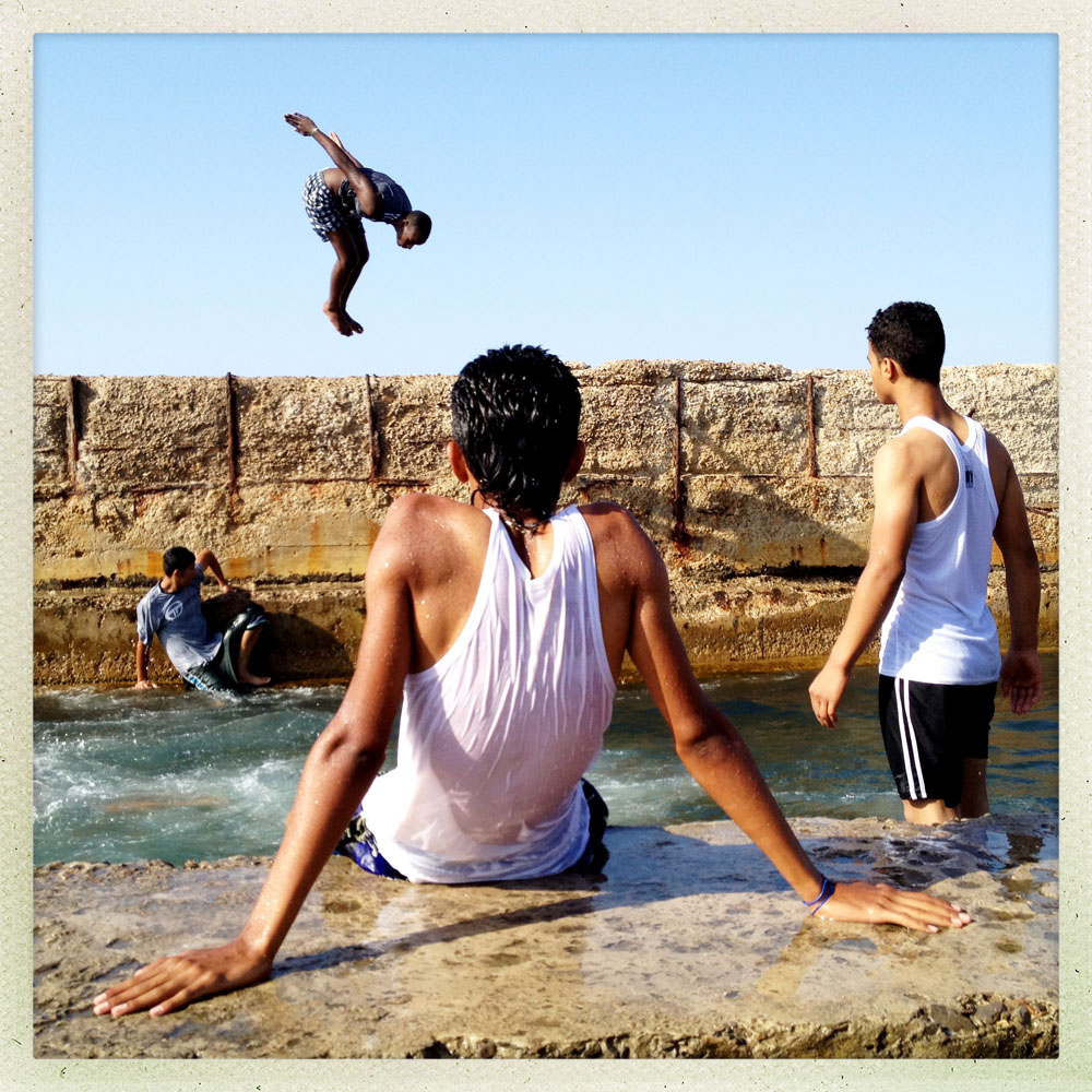 TRIPOLI, LIBYA - JULY 3: Young Libyans swim on a rubble strewn stone cornish during a hot summer day on July 3, 2012 in Tripoli, Libya.