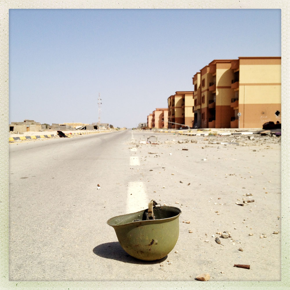 TAWARGHA, LIBYA - JULY 5: A bullet pierced helmet lies  in the middle of the street in the midst of an abandoned city  just south of the Misrata on July 5, 2012 in Tawargha, Libya. After defeating Gaddafi government forces, Rebels from Misrata destroyed Tawargha, accusing residents of supporting Gaddafi and committing atrocities alongside pro-government forces in Misrata. All residents were forces to flee, many now virtual prisoners in IDP camps setup throughout the country. Many Tawarghan men are still targets of revenge killings by Misratan Militias and sympathizers.