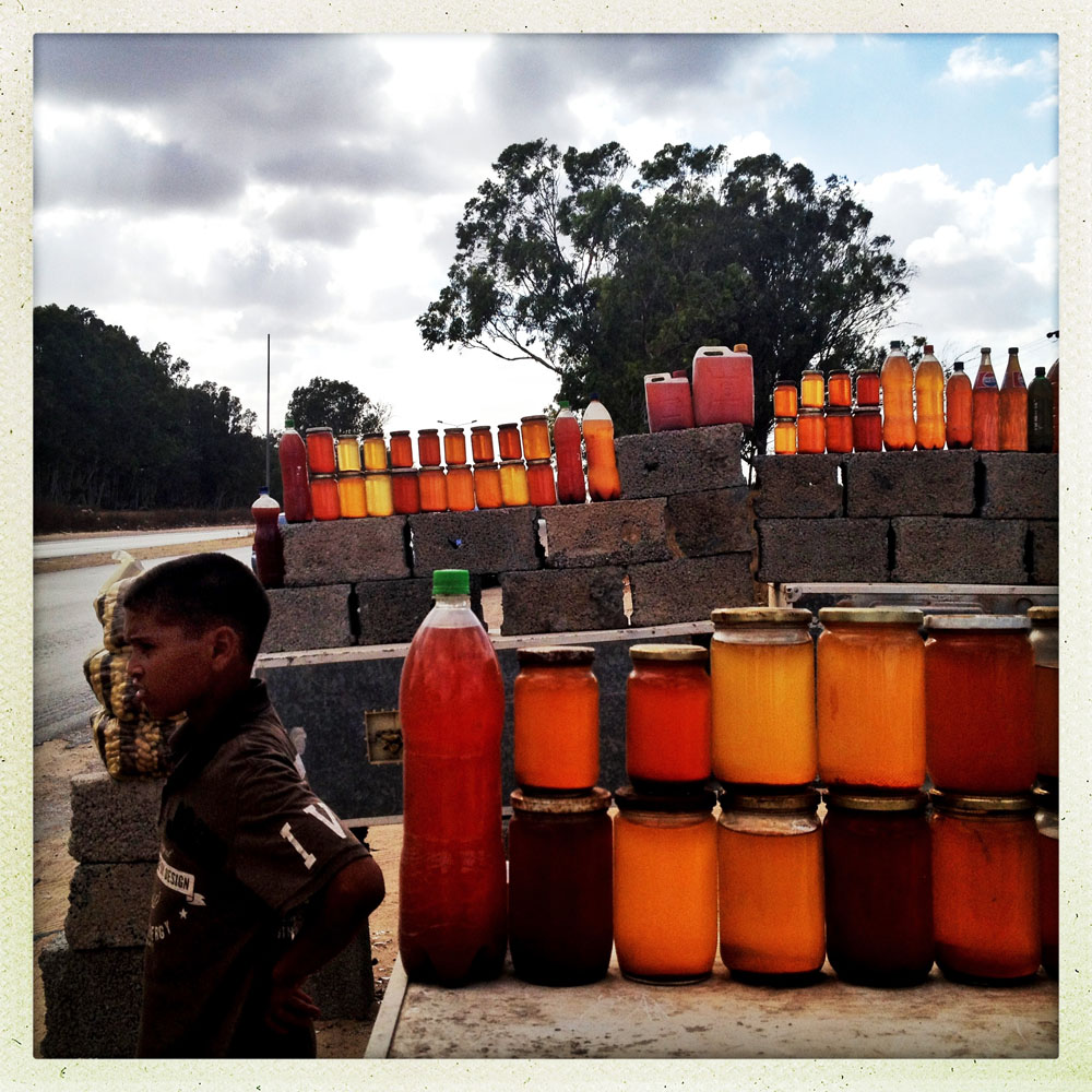 HOMS, LIBYA - JULY 17: A Libyan boy sells fresh honey along the road to Tripoli on July 17, 2012 in Homes, Libya.