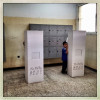 BENGHAZI, LIBYA - JULY 7: A young boy stands next to a voting booth while his father votes in the first free Libyan elections in decades on July 7, 2012 in Benghazi, Libya.