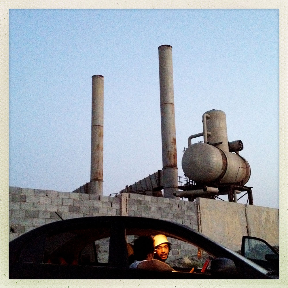 ZUWARAH, LIBYA - JULY 13: Young Libyan men relax in a car outside an abandoned and unsecured refinery abutting the sea. Many young men escape to swimming holes and secluded spots to relax away from the post revolutionary chaos of Tripoli.