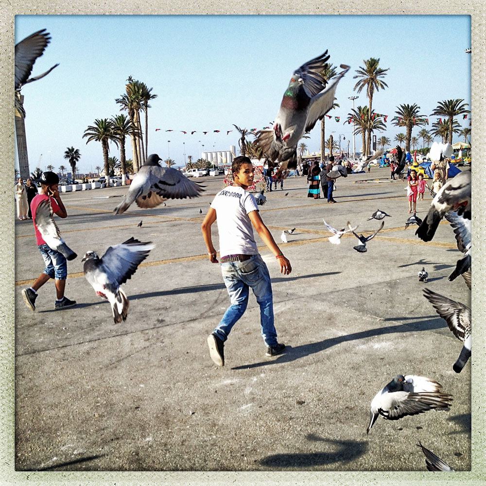 TRIPOLI, LIBYA - JULY 3: A Libya teen runs through a flock of birds in the newly renamed Martyrs Square in the center of the Old CIty on July 3, 2012 in Tripoli, Libya.