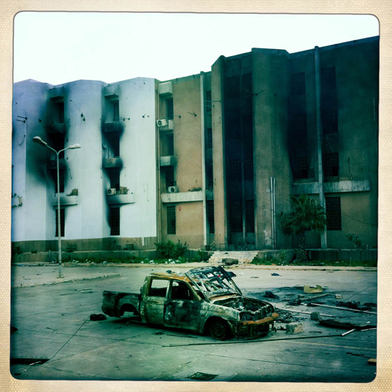 A torched car lies in front of the burnt out remains of a Libyan government building.