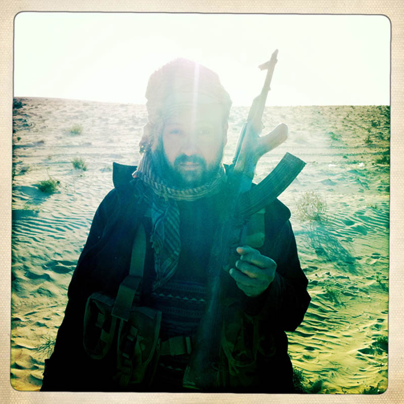 A Libyan rebel stands on the front lines during a lull in fighting between regime loyalists and rebel fighters.