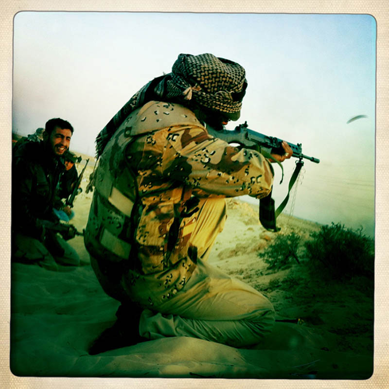 A Libyan rebel fires his weapon from behind the cover of a sand berm.