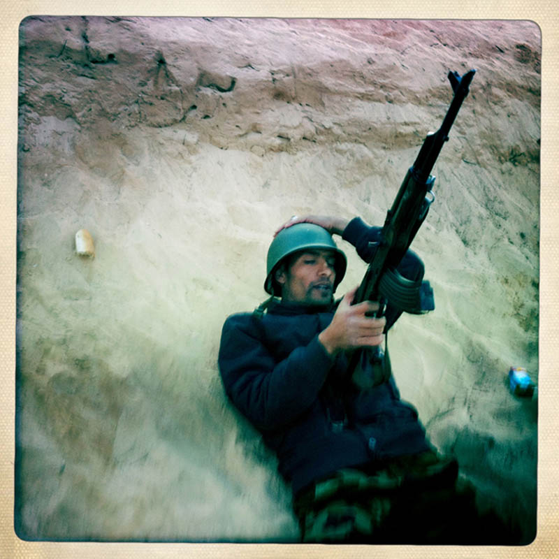A Libyan rebel takes cover behind a sand berm as pro-Gaddafi forces shell their position on the outskirts of Ajdabiya, Libya.