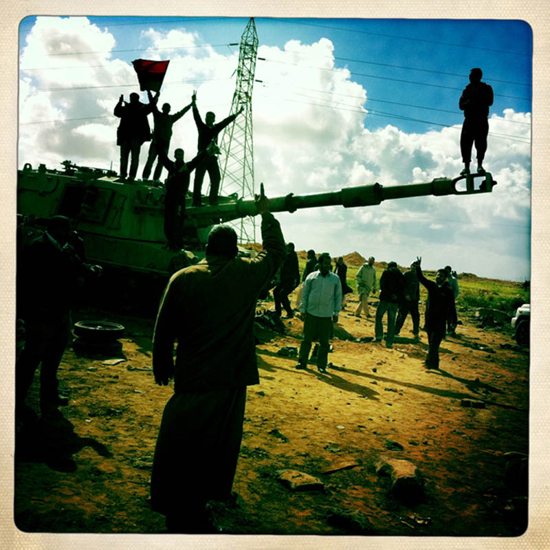 Libyan civilians walk and climb on the rubble of destroyed pro-Gaddafi army vehicles and weapons following NATO airstrikes.