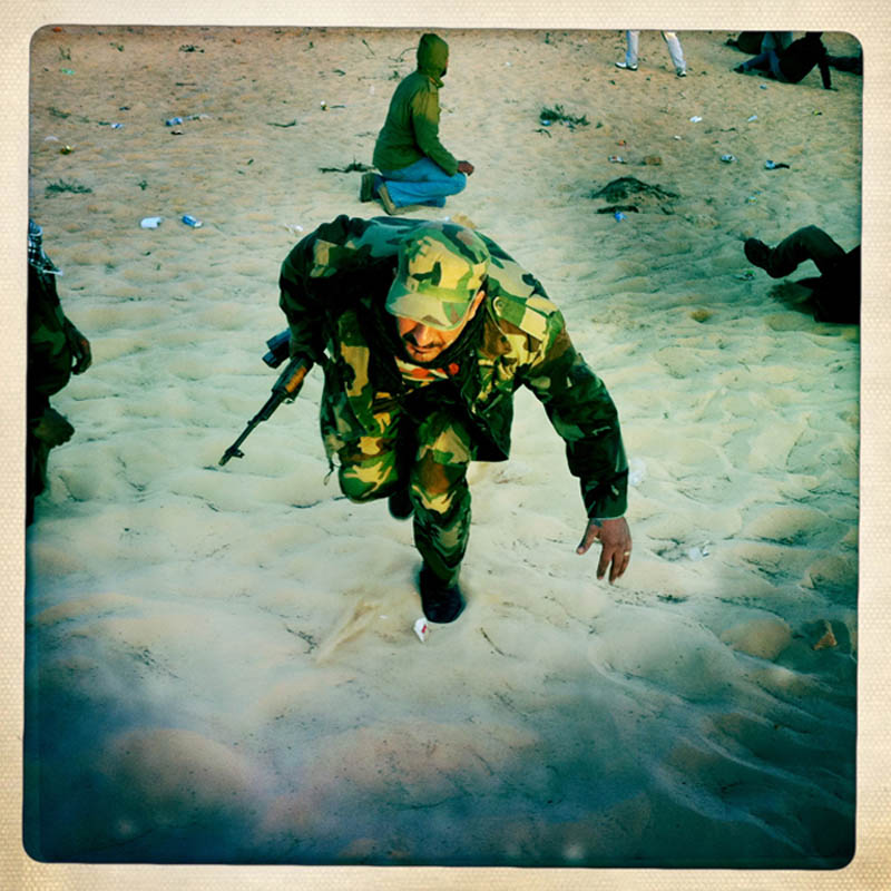 A Libyan rebel runs across the open plain of the desert looking for cover, during a battle with pro-Gaddafi forces.