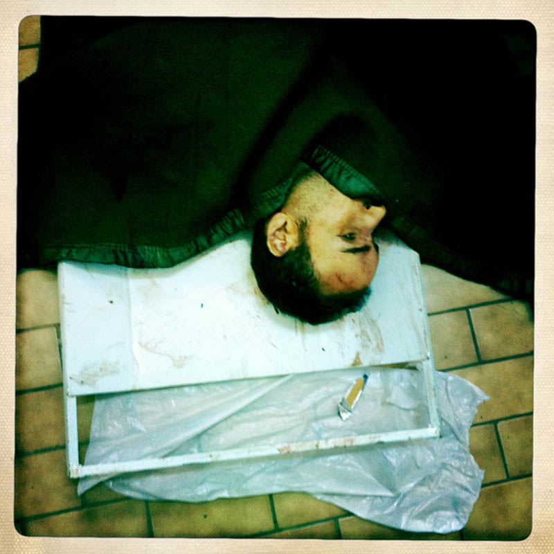 A dead Libyan lies on the floor of a hospital morgue.