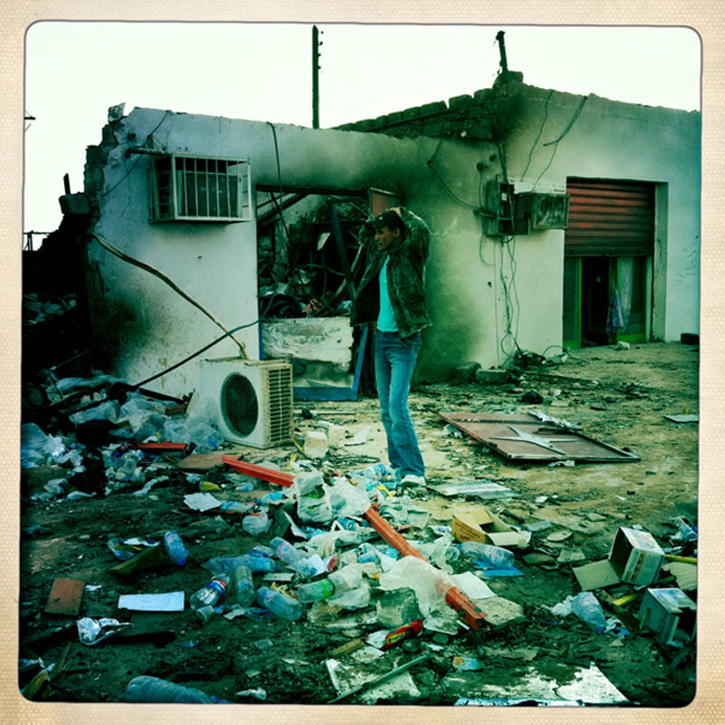 A Libyan civilian stands amidst the rubble of a war-ravaged city street in Brega,