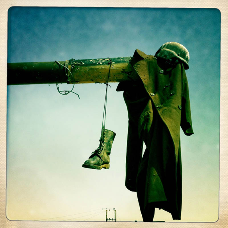 Abandoned and bullet ridden clothes of Gaddafi loyalist soldiers hang from a destroyed tank following a rebel victory.