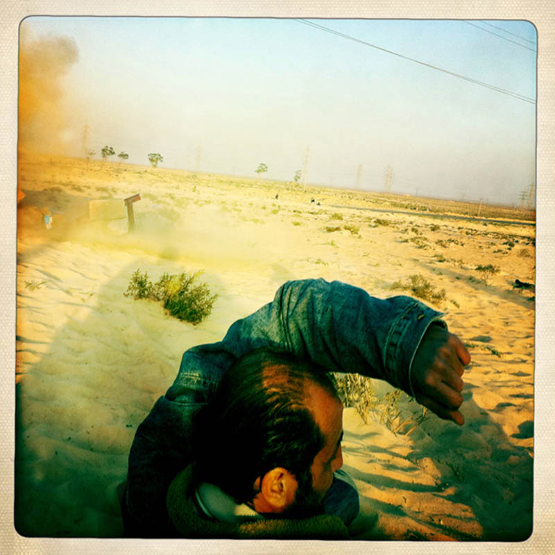 A Libyan civilian covers his face as a mortar explodes near his position during a pitched battle between Libyan rebels and Gaddafi loyalist forces