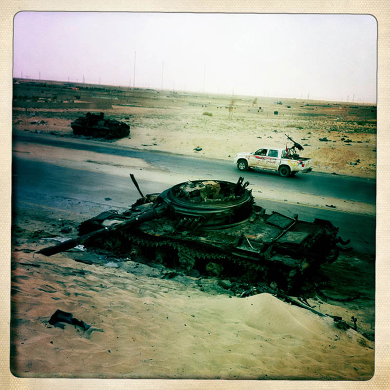 A rebel technical drives past the remains of destroyed Gaddafi loyalist tanks.