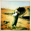 A Libyan man walks past the remains of Gaddafi loyalist tanks that were targeted by NATO airstrikes.