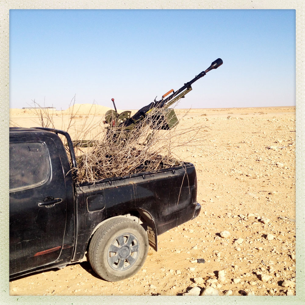 BIR DUFAN, LIBYA - JULY 15: A dead brush sits in the back of a rebel truck, along with a heavy weapon used by soldiers from Zlintan and members of the Libyan Shield, a military umbrella group of various rebel militias, as they patrol the volatile desert region bordering the Gaddafi loyalist enclave of Bani Walid and revolutionary Misrata on July, 15, 2012 in Bir Dufan, Libya.